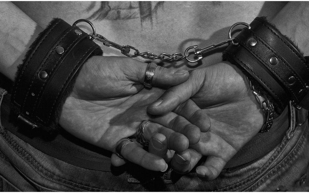 Ein männlicher BDSM-Sklave ist mit schwarzen Lederhandschellen am Rücken gefesselt.